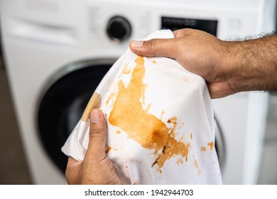 White cotton shirt A lot of stains, stains, coffee stains, man's hand holds the shirt up and spreads it to look dirty Must be brought to the washing machine