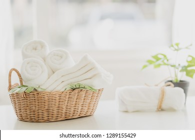 white cotton towels in basket  with green plants on white counter table inside a bright bathroom background, copy space for product display montage