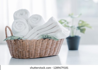 white cotton towels in basket with green plant on white counter table inside a bright bathroom background, copy space for product display montage