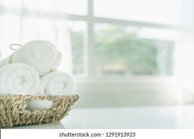 white cotton towels in basket on white counter table inside a bright bathroom background, copy space for product display montage