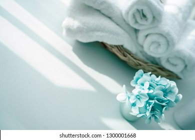 white cotton towels in basket with patel plant on white counter table inside a bright bathroom background, copy space for product display montage