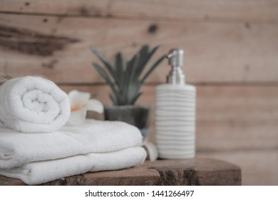 white cotton towels with ceramic soap, shampoo bottles and on wood counter table inside a liveing background.