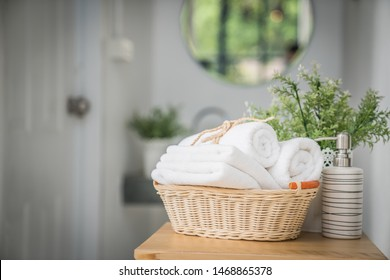 White cotton towels, ceramic soap, shampoo bottles and with green plant on wood counter table inside a bright living room background
