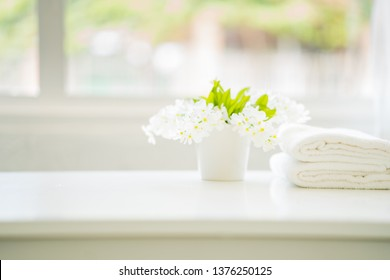 white cotton towels with white flowers on white counter table inside a bright bathroom background. For product display montage
