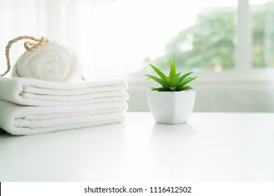 White cotton towels and green plant on white counter table inside a bright bathroom background.