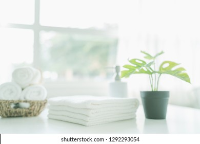 white cotton towels with green plant on white counter table inside a bright bathroom background, copy space for product display montage