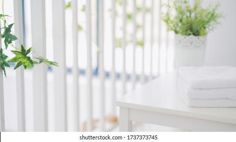 Handtücher aus weißer Baumwolle mit grünen Pflanzen auf weißem Tresentisch, Kopierplatz für die Produktpräsentation