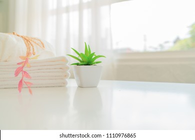 White cotton towels and green ppant on white counter table inside a bright bathroom background.