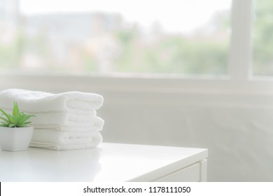 white cotton towels on white counter table inside a bright bathroom background. For product display montage.