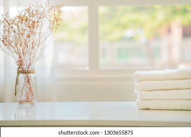 white cotton towels on white counter table inside a bright bathroom background. For product display montage