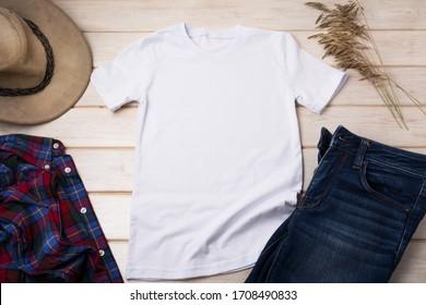 White men's cotton T-shirt mockup with checkered tartan plaid shirt, dry grass and cowboy hat. Design t shirt template, tee print presentation mock up