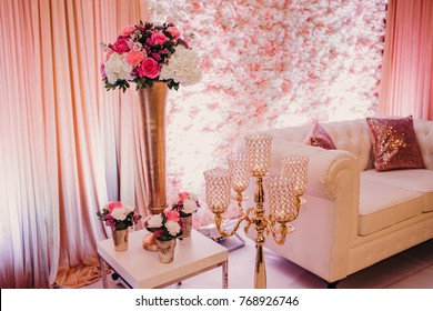 White couch decorated with sparkling pink pillows stands before a wall with flowers and waits for newlyweds
