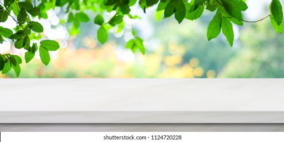 White counter, kitchen table top and blur perspective green tree in summer nature background, White marble counter for kitchen product display backdrop, Stone shelf, table top surface for banner