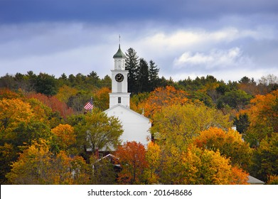 White country church and American flag surrounded by autumn colors in New England