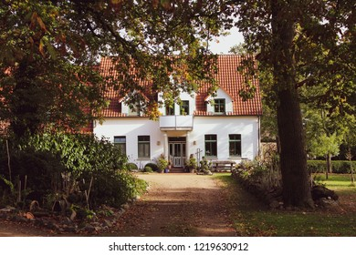 White country house with tiled roof, green window frames, balcony and columns at the entrance, idyllic environment with trees and autumn leaves, a broad path leads to the premises