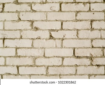 White country style brick wall background photograph. Rough textured bricks painted white in farmhouse style, an authentic photograph shot outdoors with natural light.
