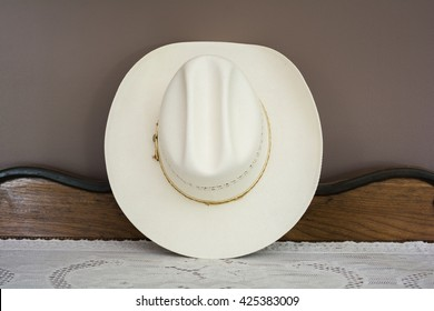 A White Cowboy Hat on an Antique Cabinet Front View