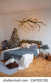 White cozy modern bedroom with holiday decoration. Wooden bed in scandinavian style room with festive Christmas tree in a pot and led garland lights. Home christmas decor.