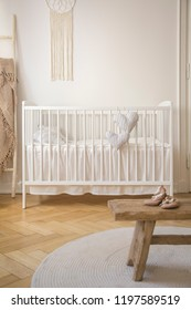 White cradle and shoes on wooden stool in baby's bedroom interior with round rug. Real photo