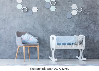 White cradle standing next to a grey armchair against the wall decorated with honeycombs in a baby room interior