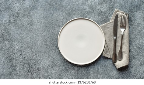 White craft plate, cutlery and napkin on white stone table. knife and fork on beige napkin. Top view, copy space. Table setting. background for menu, layout, recipe background, food flat lay