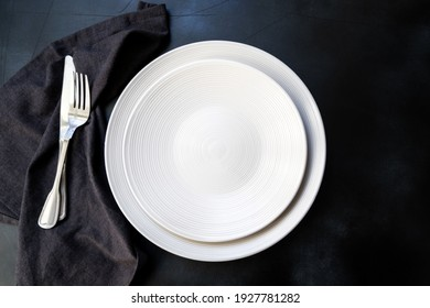 White craft plate, cutlery and napkin on dark  table. Top view, copy space, Table setting. background for menu, layout, place for text , recipe background