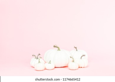 White craft pumpkins of different sizes on a pink background.
