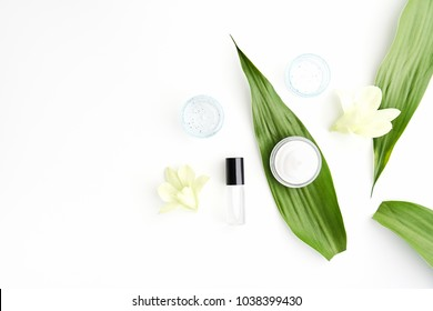 White cream bottle placed, Blank label package for mock up on a green foliage background and flowers. The concept of natural beauty products.