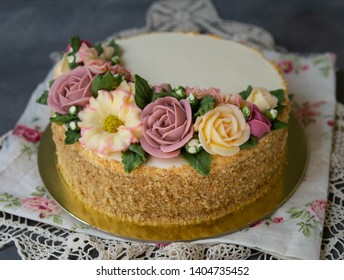 White cream honey cake decorated with buttercream flowers peonies, roses, chrysanthemums, scabiosa on gray background with lace fabric. Close up, selective focus.