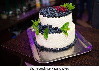 White, cream wedding or birthday cake with flowers and love title