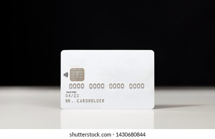 White credit card on glossy table over black background