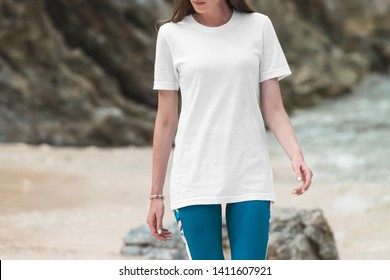 White crew neck t-shirt on a young woman in leggins, front view mockup, on a beautiful beach