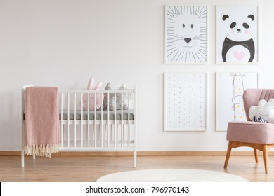 White crib with pink blanket and decorative cushions standing in cute baby room with posters