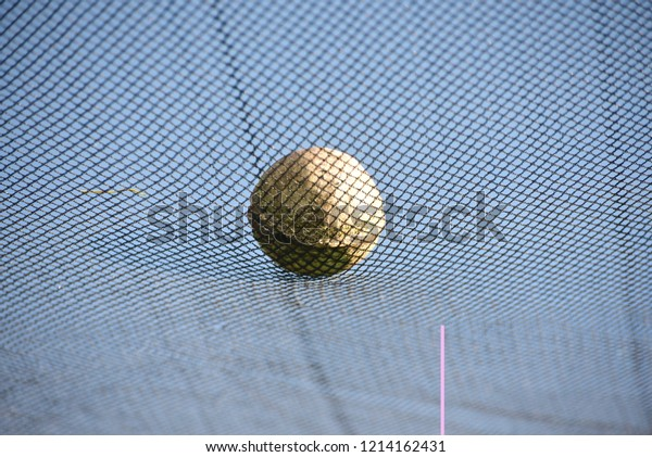 A white cricket ball on top of a nylon nets unique blurry photo