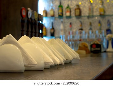 White crockery and napkins on a wooden bar counter ready to be served to clients with rows of bottles on shelves behind
