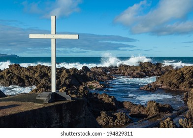 White cross by a rocky coastline with roaring waves too.