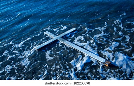 White cross floating on water with some white sea foam around it.