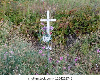 White cross installed in the overgrown, flowering autumn shrubs after a fatal car accident. Good image for death, loss, mourning, religion, faith, burial and remembrance.