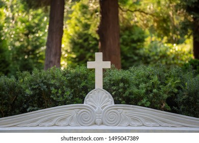 White cross on a tombstone with ornaments