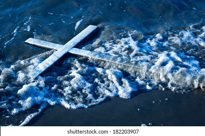 White cross that has been wash up on a beach.