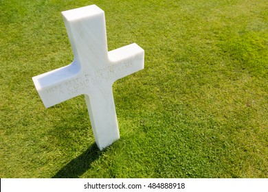 """White cross for an unknown soldier at the american cemetery in Colleville sur mer, Normandie, France: """"here rests in honored glory a comrade in arms known but to god"""""""