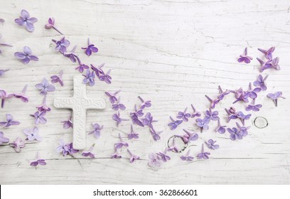 White cross and violet or purple lilac blossom on old background for a condolence card.