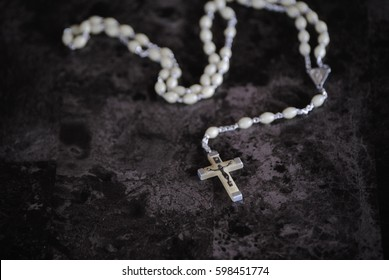 White crucifix rosary, with white beads.