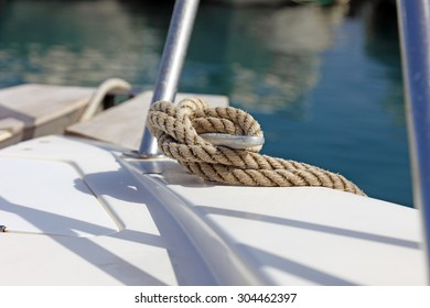 White cruise sailing boat hold with watercraft rope knot on dock, strong fixing yacht ships for safety.