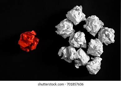 White crumpled paper ball with different red crumpled paper ball on black background