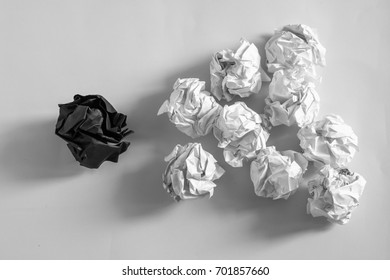 White crumpled paper ball with different black crumpled paper ball on white background