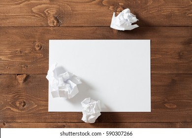 White crumpled paper on a wooden table.