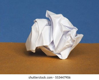 white crumpled paper sheet over brown and blue paper background with copy space