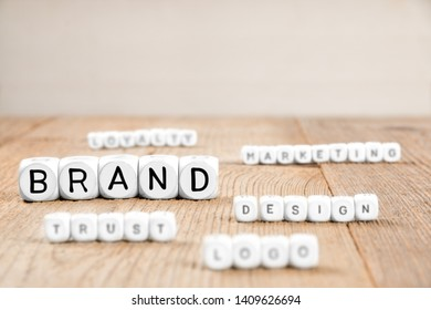 White cube blocks with Brand, Logo and Trust concept related words on wooden surface, focused on Brand cube
