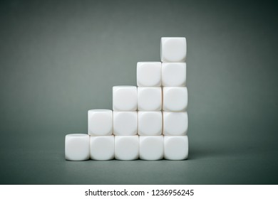 White cubes stacked in stair pyramide step by step on grey colored background